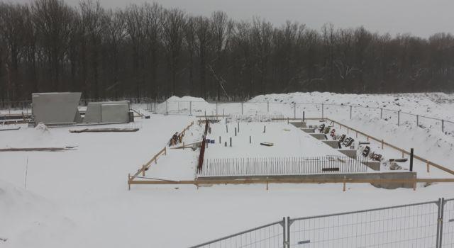 Bouwterrein op de toekomstige locatie in winterse sfeer