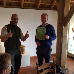 Boswachter Tim Boerrigter-van Weert reikt het certificaat 'Inleiding beheer natuurgrasland 'uit aan agrarisch ondernemer Arend Bouwman uit Staphorst.