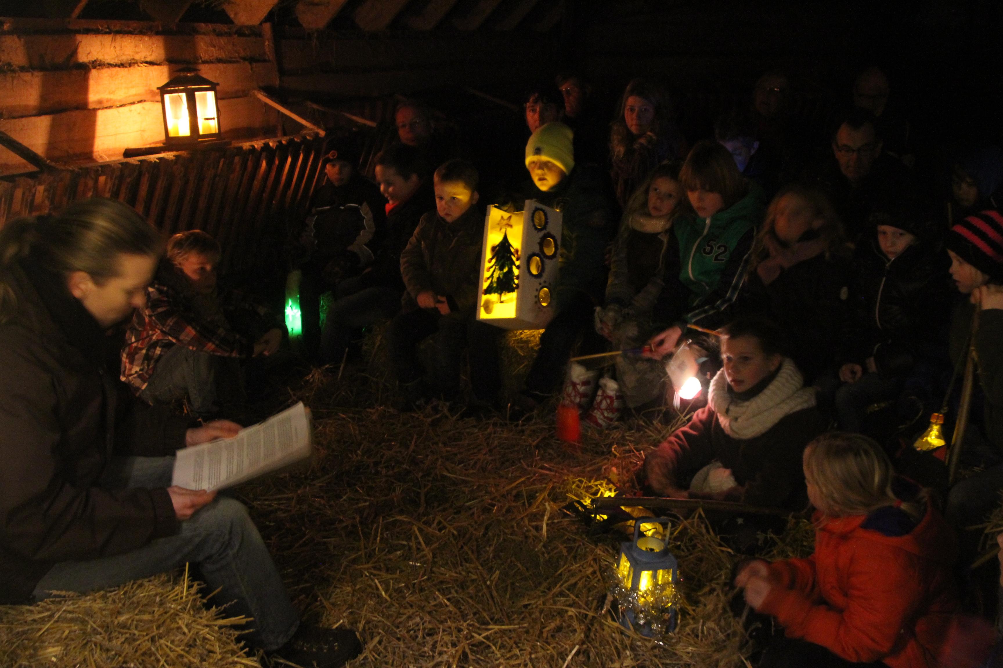 Lampionnetjes én kinderen stralen in de schaapskooi op midwinteravond